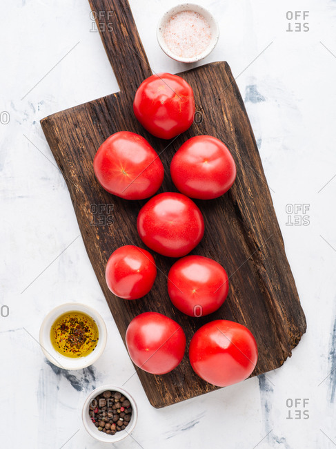 Fresh tomatoes on dark wooden chopping board with spices and pink salt