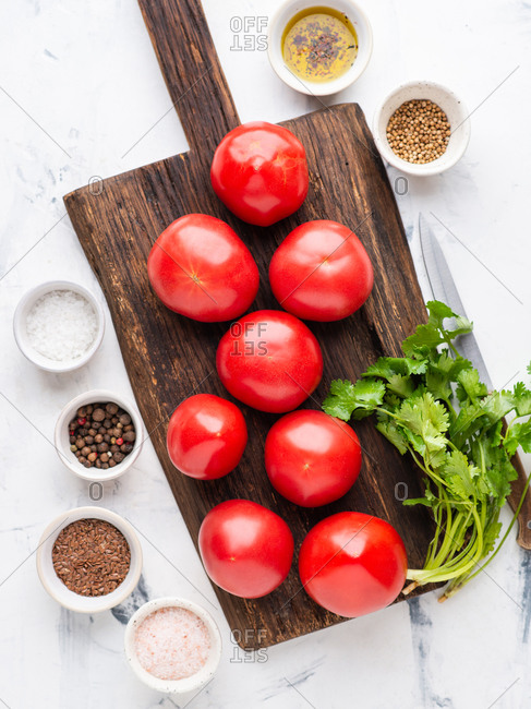 Fresh tomatoes on dark wooden chopping board with spices and cilantro