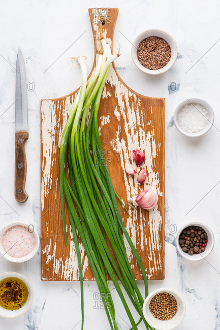 Spring onion on wooden cutting board and small ceramic bowls with various spices over white background viewed from above