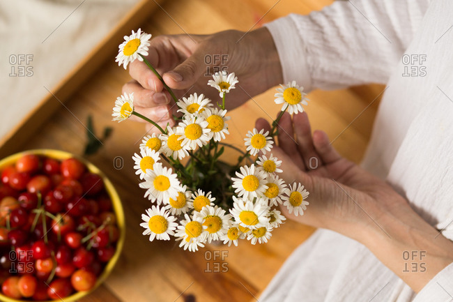Close up of woman arranging flowers in a vase beside a bowl of cherries