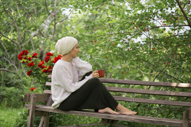 Woman sitting on a bench drinking coffee in garden