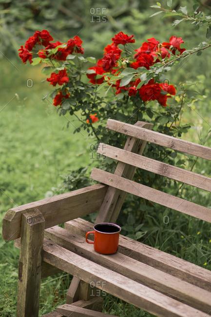 Red coffee mug on wooden bench in garden