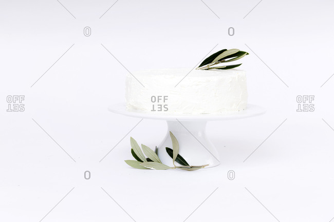 White cake topped with olive leaves on white background