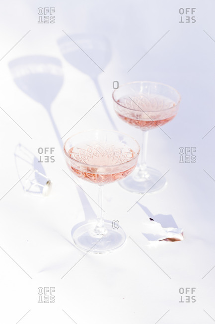 Elevated view of champagne served in two coupe glasses on light background