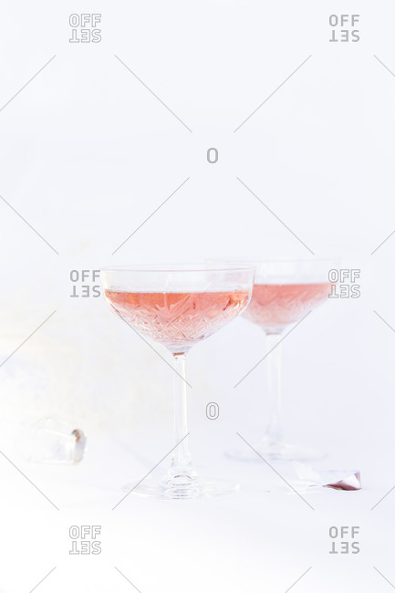 Champagne served in two coupe glasses on light background