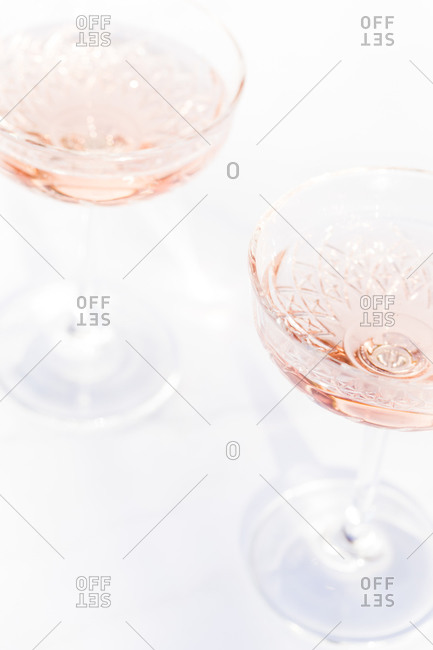 Close up of champagne served in two coupe glasses on light background