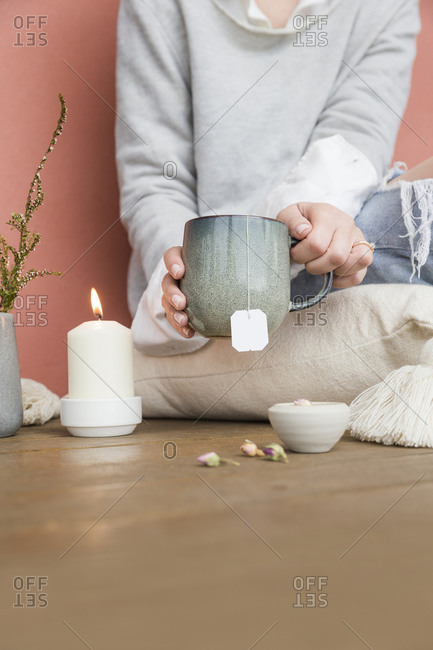Woman drinking herbal tea beside a lit candle