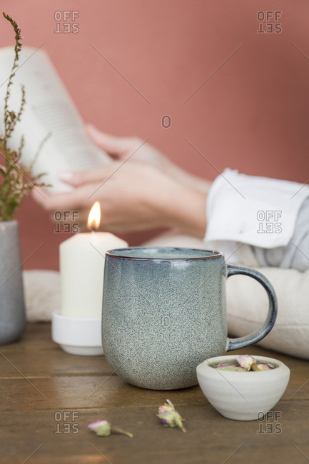Woman reading a book drinking herbal tea beside a lit candle