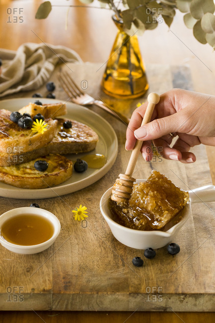 Woman stirring honey beside French toast topped with blueberries and honey