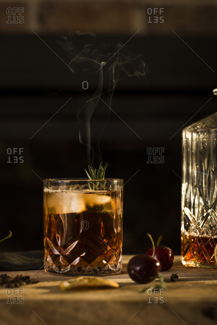 Whiskey cocktail garnished with smoking rosemary