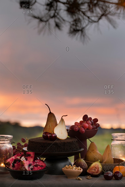 Picnic with chocolate cake and fruit served with wine at sunset