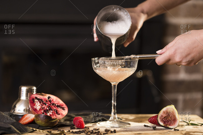 Woman preparing a fruity pink cocktail