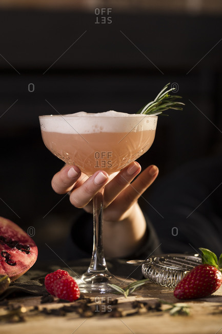 Woman holding a fruity pink cocktail