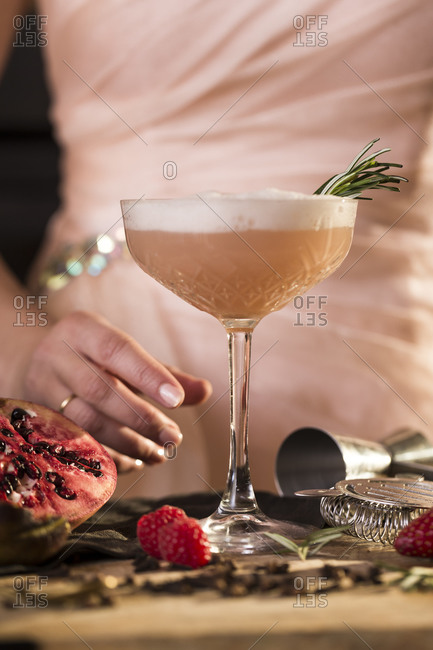 Woman standing behind a fruity pink cocktail