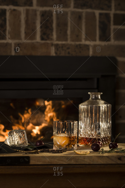 Whiskey cocktail being made beside fireplace