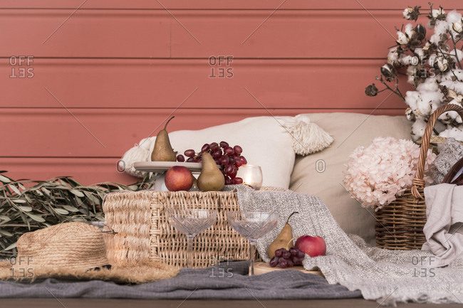 Cozy picnic served on blanket with fruit beside cotton plant and flowers