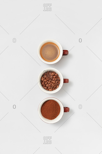 Different stages of coffee three ceramic cup with beans, freshly ground powder and freshly brewed aromatic drink on a white background, copy space. Top view.