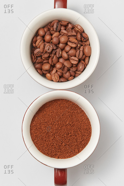 Close-up view different stages of coffee - two ceramic cups with beans and freshly ground coffee powder on a white background, copy space. Top view.
