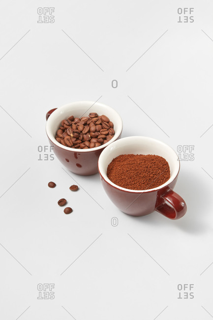 Two ceramic cups with aromatic beans and freshly ground coffee powder on a white background, copy space.