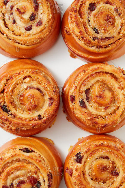 Bakery background with freshly baked homemade sweet delicious rolled buns with raisin on a light grey background. Top view. Close-up view.