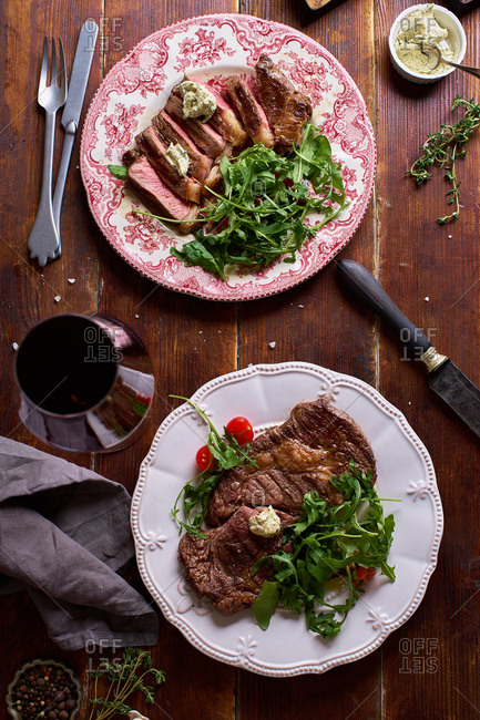 Overhead view of grilled beef steakes served with fresh salad, herb butter and a glass of red wine