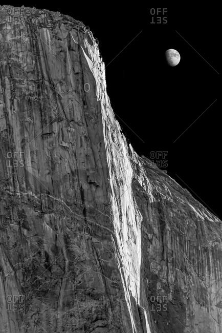Moon rising behind El Capitan granite rock formation in Yosemite, California
