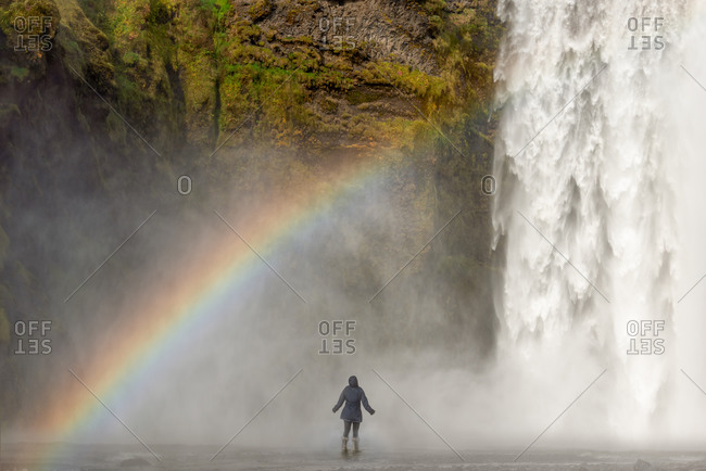 Adventurous woman standing very close to Skogafoss waterfall with rainbow, Southern Iceland