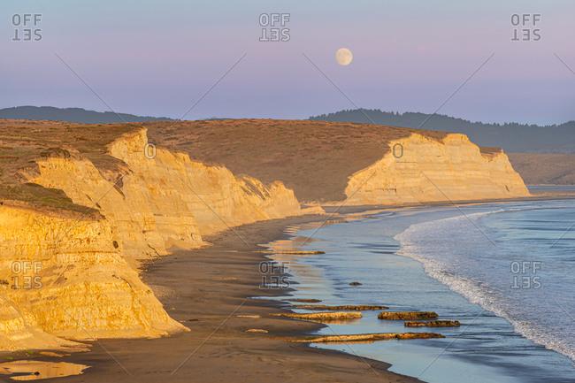 Full moon rising behind the cliffs at Drakes Beach in Point Reyes, California