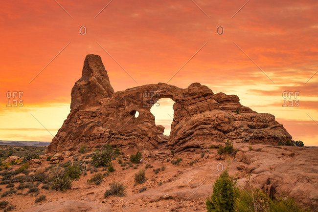Turret Arch in Arches National Park under orange sunset sky, Utah