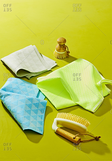 Cleaning microfiber cloths and sponges on green background