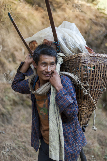 Namche Bazaar, Namche, Khumbu, Everest Region, Nepal - November 19, 2008: A porter carries a Doko in the Everest region of Nepal
