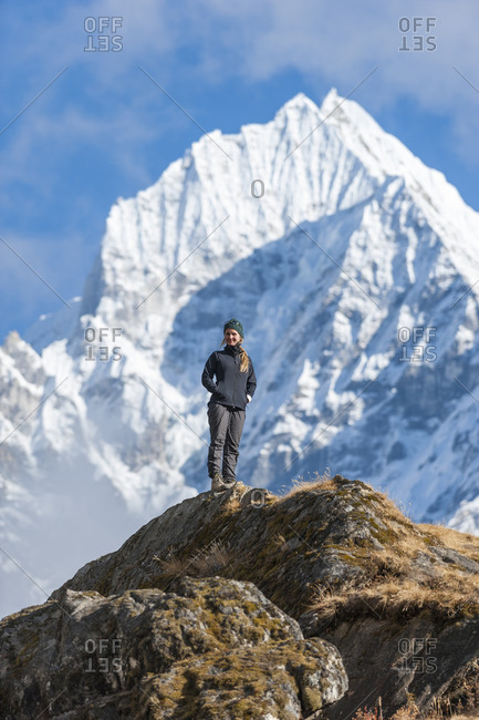 A woman trekking in Nepal enjoys the views above Namche in the Everest region with the big peak of Thermserku in the background
