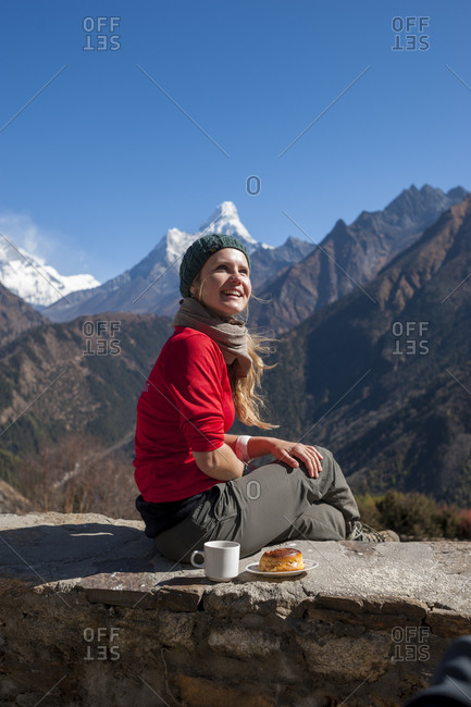 A trekker with coffee and a pastry near Phurte in the Everest region with views of Ama Dablam in the distance