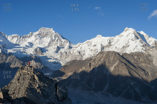 A girl in a red  jacket on the summit of Gokyo Ri with a view of Cho Oyu in the distance in the Everest region of Nepal