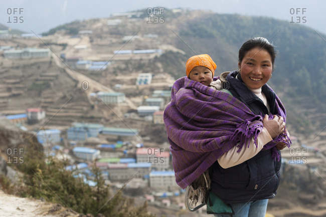 Namche Bazaar, Namche, Khumbu, Everest Region, Nepal - April 7, 2009: A woman carries her baby in a blanket with Namche visible behind