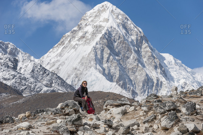 A trekker on their way to Everest Base Camp takes a break with views of Pumori in the distance