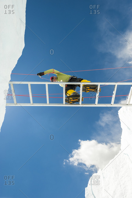 A climber makes his way across a crevasse using a temporary ladder