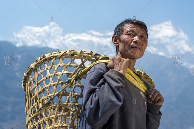A Nepali man in the Everest region carrying a Doko which is a traditional style of basket made of bamboo and carried on the head with a Namlo or head strap