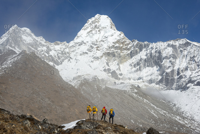 A team of climbers gaze up at the prospect ahead; Ama Dablam in the Khumbu region of Nepal