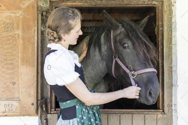 Farmer with dirndl strokes a horse