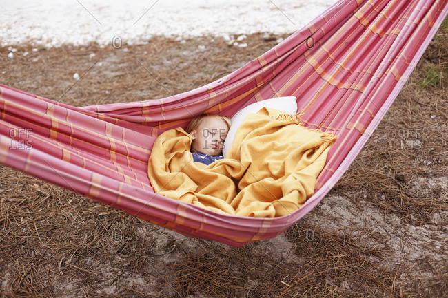 Little boy is sleeping in a hammock