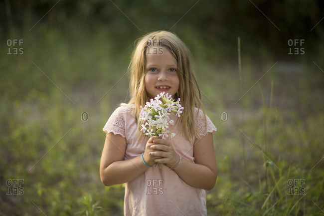 Little girl with bouquet in the forest