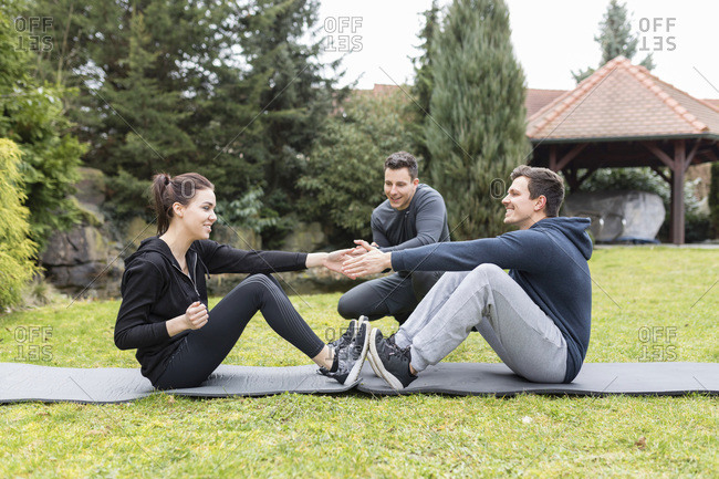 Couple trains with personal trainer in the garden