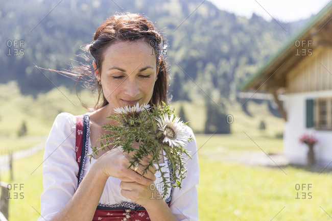 Farmer with dirndl smells at a silver list
