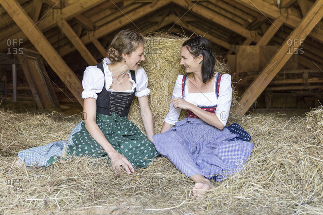 Two friends with dirndls are chatting on the hayloft