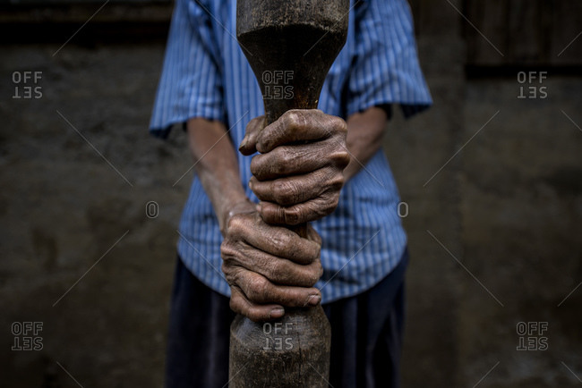 Woman holds spear to rice pounding, Cordillera, northern Luzon, Philippines