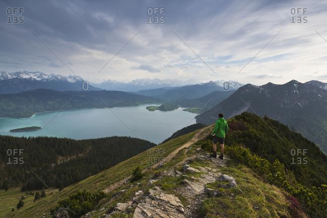 Hiker looks out to Lake Walchensee, Upper Bavaria, Bavaria, Germany, Europe
