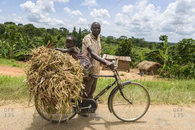 October 14, 2014: Grandfather and granddaughter on bicycles, Western Uganda, Africa