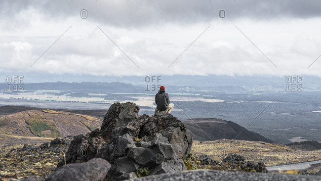 April 8, 2016: Man looks out from rock from Ruapehu, New Zealand