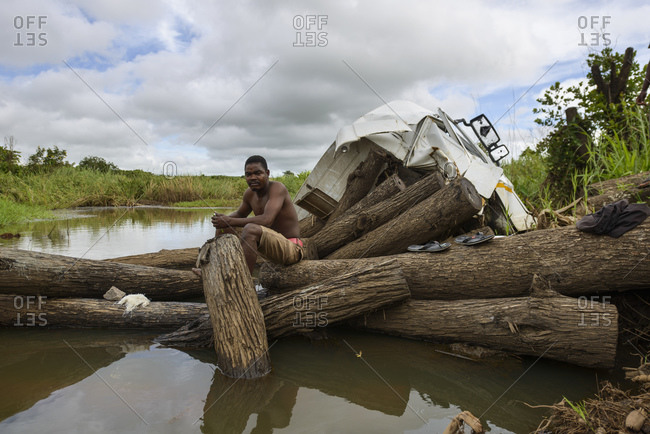 January 13, 2015: Man sitting on tree trunks on a river, Mozambique, Africa